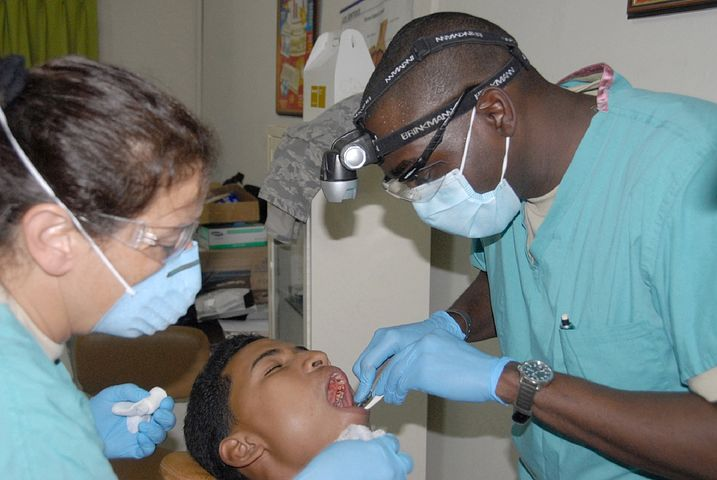 2 dentists checking a patient's mouth