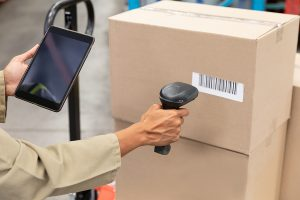 Female worker scanning package with barcode scanner while using digital tablet in freight and distribution warehouse.
