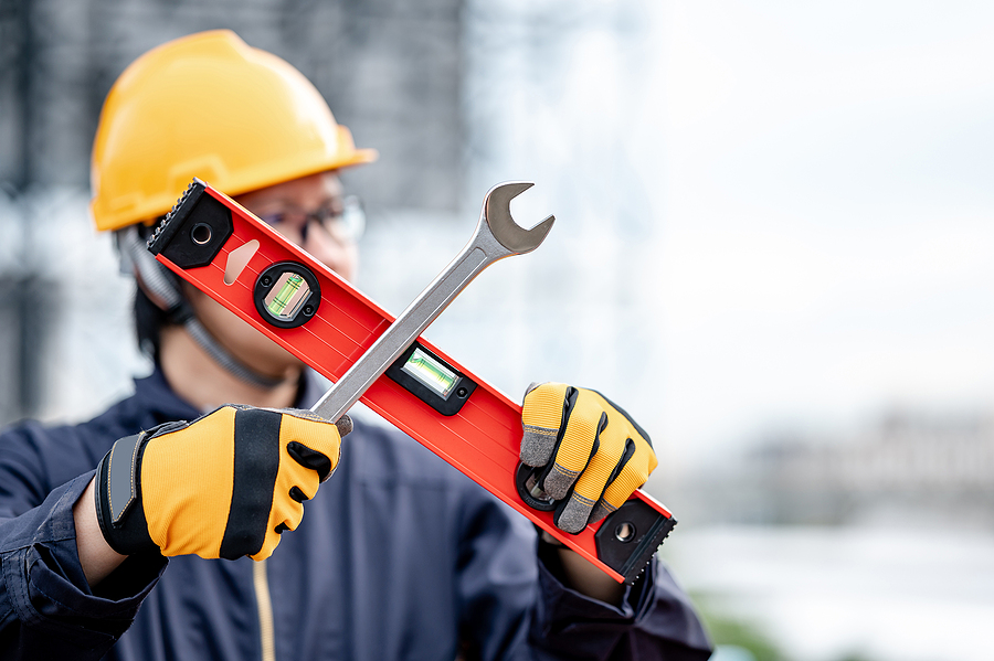 Male mechanic wearing protective suit and helmet holding wrench and level tool in cross shape at construction site.