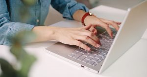Copywriter working for a Sydney SEO company writing and typing in her laptop