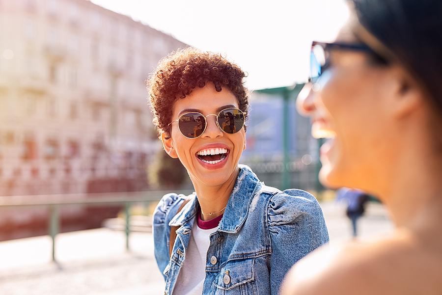 Two women happily wearing Garrett Leight sunglasses